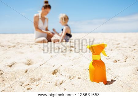 Closeup On Sunscreen Bottle On Beach. Family In Background
