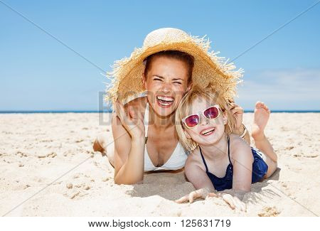 Smiling Mother And Daughter Laying On Beach Under Big Straw Hat