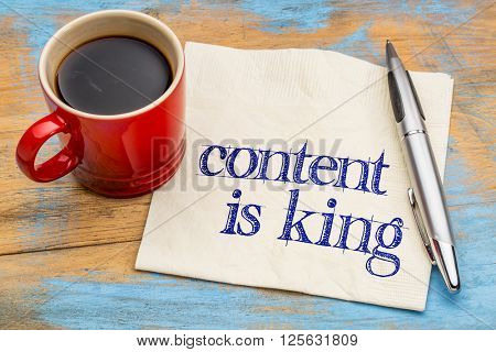 content is king - writing, blogging and publishing concept - handwriting on a napkin with a cup of coffee