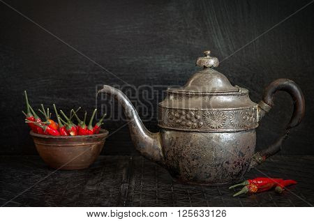 Food background with old antique iron kettle and hot chili pepper. Dark food background. Vintage food background.