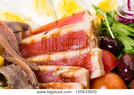 Delicious nicoise salad with anchovies and olives. Macro. Photo can be used as a whole background.