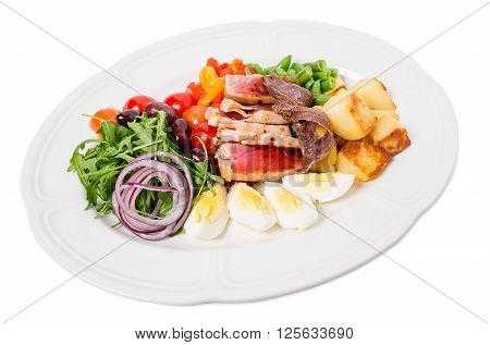 Delicious nicoise salad with baked potatoes and french beans. Isolated on a white background.