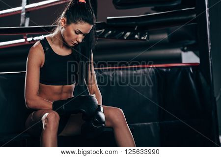 brunette woman wearing black sportwear and boxing gloves posing near ring, looking at gloves