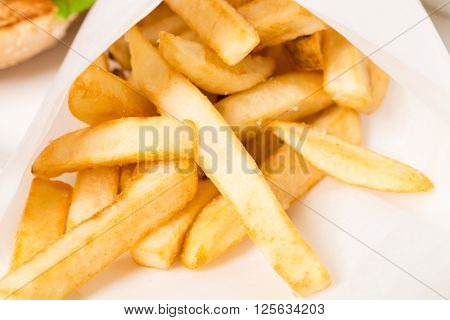 Closeup of french fries in a paper wrapper. Macro. Photo can be used as a whole background.