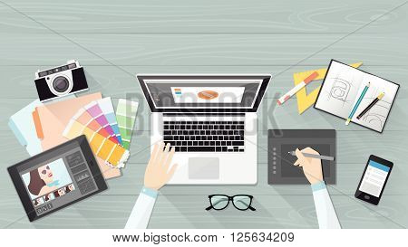 Professional creative graphic designer working at office desk he is designing a vector illustration using a laptop