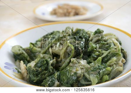 stir-fried chicory served in white dish with in the background a dish of cannellini beans ** Note: Shallow depth of field