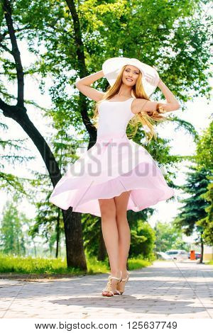Happy beautiful young woman in light summer clothes enjoying sunny summer day. Beauty, fashion.