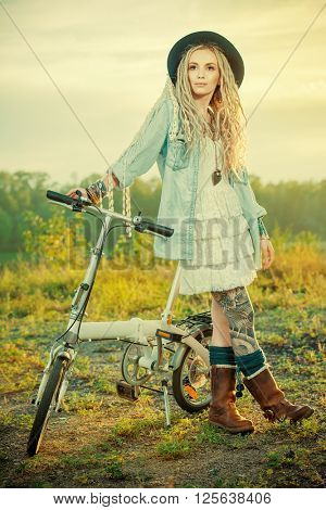 Carefree smiling girl in boho style clothes rides a bicycle. Beauty, fashion. Summertime.
