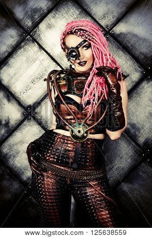 Portrait of an attractive steampunk woman over grunge background.