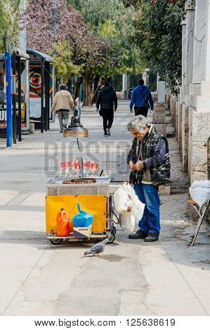 ATHENS GREECE - MAR 27 2016: Man selling traditional heart shaped candy sweets on the streets of Athens Greece