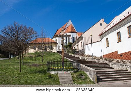 Traditional slovak village built on a hill with a church on the top of it. Wooden cross beside the stairs to the gothic church. Springtime with a green grass and blue sky.