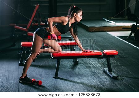 brunette woman exercising red dumbbell row at the gym