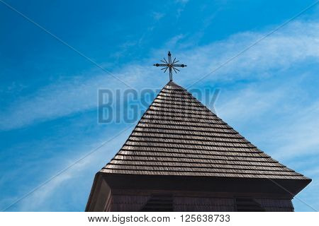 Dark brown roof made of wooden shingle with a cross on the top. Cloudy sky. Svaty Jur Slovakia Europe.