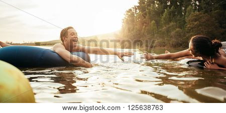 Loving young couple about to hold hands while floating on inner tubes in lake. Young man and woman on an inflatable tube in water.