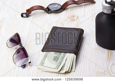 gentlemanly set:  sunglasses, perfume, wallet with money  and watch on wooden background