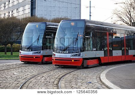 Two brand new trams on the parallel cobbled tracks in Prague, Czech republic