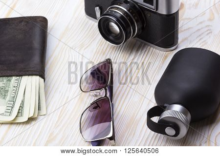 gentlemanly set:  sunglasses, perfume, wallet with money and camera on wooden background