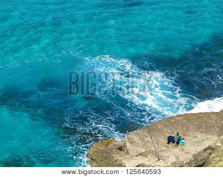 relaxed angler waiting on a rock by the clear sea