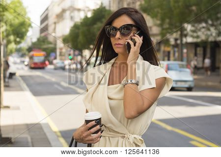 Fashionable young brunette wearing white dress and sunglasses laughs into phone on street, city, urban space