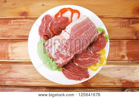 raw uncooked meat on wooden table with vegetables