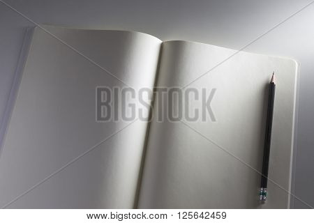 White notebook and pencil on white desk with cross lighting