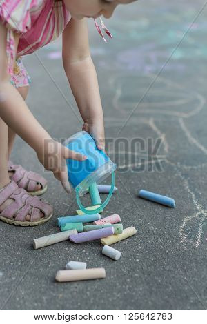 Little girl preparing for sidewalk chalk drawing on flat outdoor tarmac surface