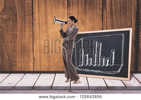 Portrait of a businesswoman shouting through a megaphone against black board on a wooden table