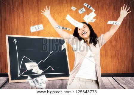Smiling woman throwing money around against black board on a wooden table