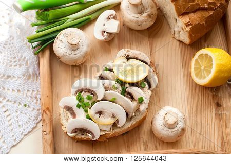 sandwich with fresh mushrooms, mayonnaise and green onion on the board. lemon slices, half mushroom, onion feathers