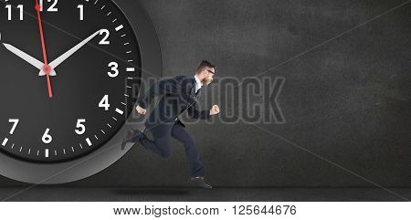 Geeky young businessman running mid air in front of a black clock and black wall