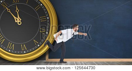 Geeky young businessman running late in front of a clock and a chalkboard