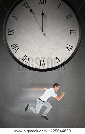 Geeky businessman running mid air on a grey background with a clock
