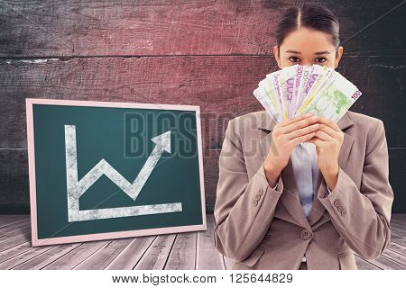 Portrait of a greedy businesswoman holding bank notes against board on a wooden floor