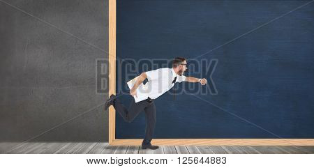 Geeky young businessman running late in front of a chalkboard