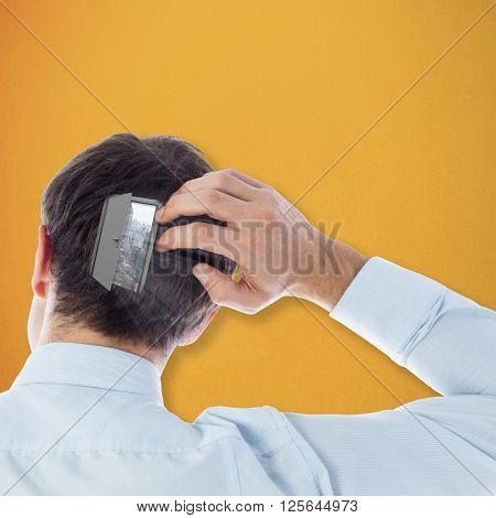 Businessman scratching his head against orange background