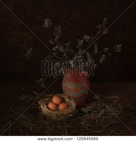 Easter scene with hay and pussy-willow in vase