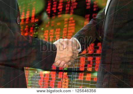 Business shaking hand on finacial graph background.