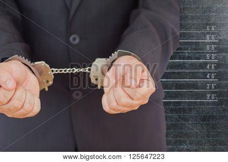 Handcuffed businessman against mug shot background