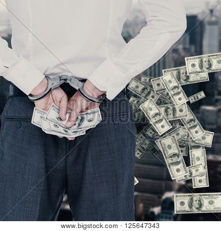 Businessman in handcuffs holding bribe against view of cityscape