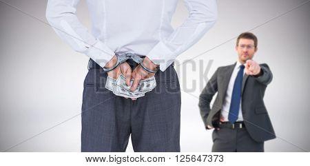 Businessman in handcuffs holding bribe against grey background