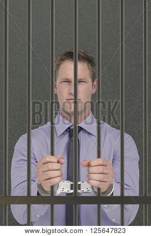 Handsome businessman wearing handcuffs against grey background