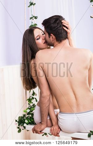 Young love couple sitting on the swing and kissing