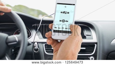 Male hand holding a smartphone against screen of satellite navigation system