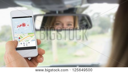 Male hand holding a smartphone against young woman in the drivers seat looking in the mirror
