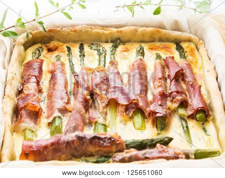 Savory pie with asparagus, prosciutto, marjoram and egg and cream mixture in a baking tin with parchment on checkered table cloth, selective focus