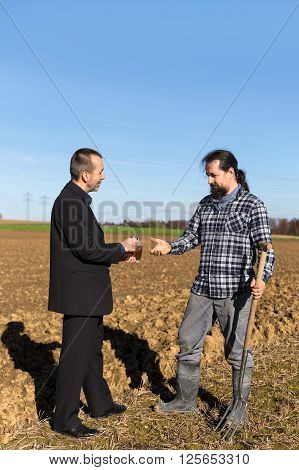 a Businessman is giving money to a farmer