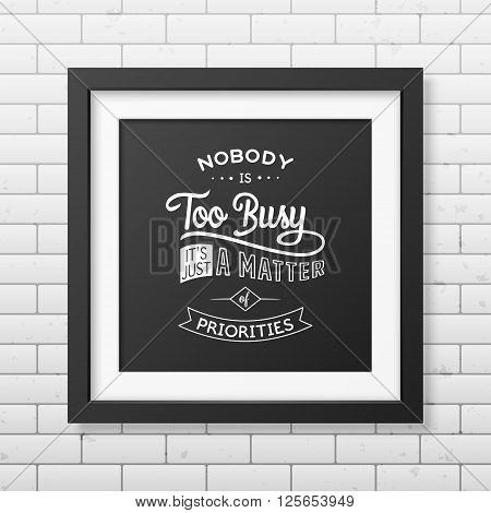 Nobody is too busy, it is just a matter of priorities - Quote typographical background in the realistic square black frame on the brick wall background. Vintage typography background, mockup for design