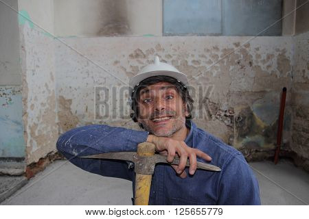 smiling Construction worker holding a pick axe