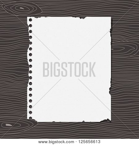 Piece of torn white notebook grainy paper is sticked on dark wooden wall or desk.