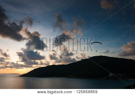 Sunset with paraglider in the sky at Phuket Thailand